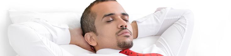 Man sleeping comfortably in a hotel room